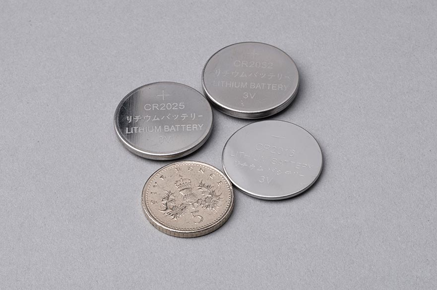 Button batteries next to 5p coin