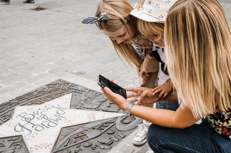 Parent and child taking photo of star plaque