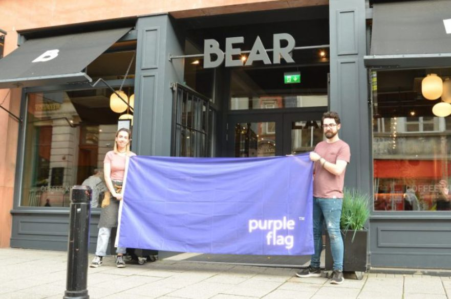 Bear Cafe staff holding purple flag