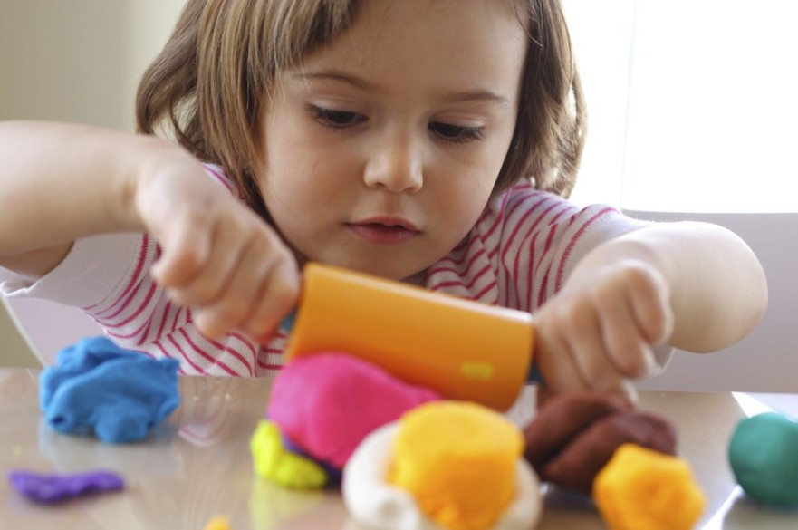 Child playing with plasticine