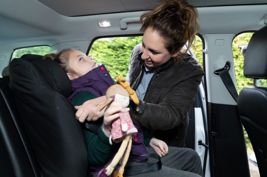 Parent helping disabled child with car seat