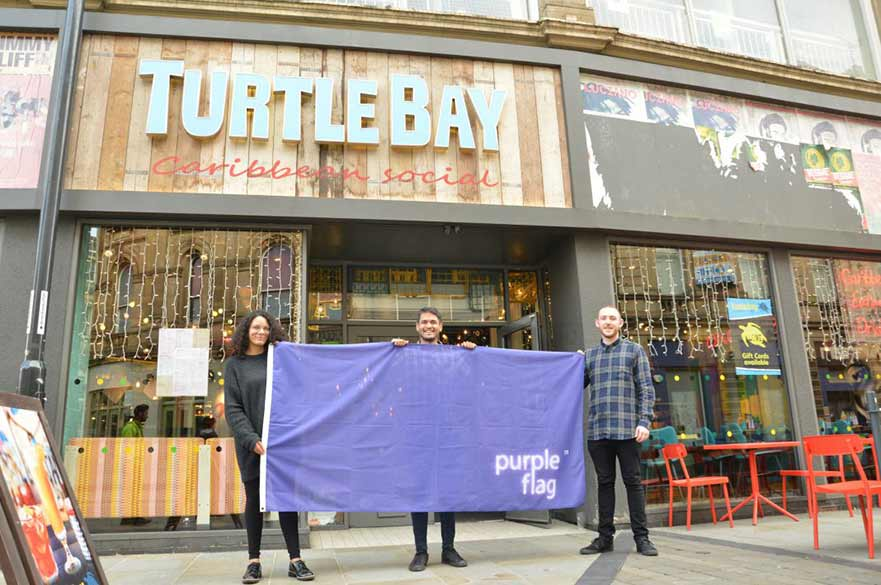 People holding flag outside Turtle Bay restaurant