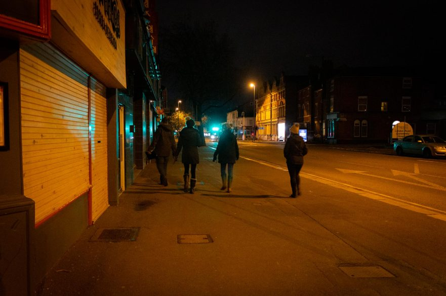 four people walking night